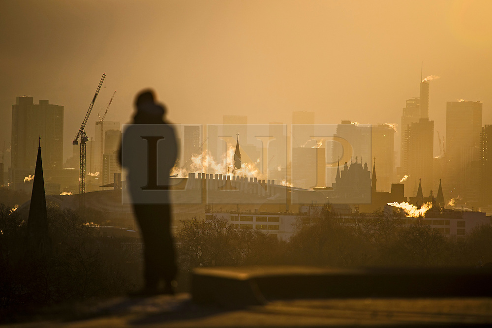© Licensed to London News Pictures. 10/02/2021. London, UK. A man watches as the sun rises over the city of London, as seen from Primrose Hill in Camden, north London, on another morning of sub zero temperatures in the capital. Photo credit: Ben Cawthra/LNP