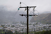 An electricity pylon and conductors stand above the Welsh town of Blaenau Ffestiniog, on 2nd October 2021, in Blaenau Ffestiniog, Gwynedd, Wales. The derelict slate mines around Blaenau Ffestiniog in north Wales were awarded UNESCO World Heritage status in 2021. The industry's heyday was the 1890s when the Welsh slate industry employed approximately 17,000 workers, producing almost 500,000 tonnes of slate a year, around a third of all roofing slate used in the world in the late 19th century. Only 10% of slate was ever of good enough quality and the surrounding mountains now have slate waste and the ruined remains of machinery, workshops and shelters have changed the landscape for square miles.