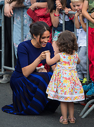 The Duchess of Sussex holds hands with a young girl during a walkabout in Rotorua on day four of the royal couple's tour of New Zealand.