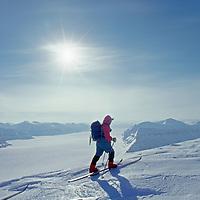 A ski mountaineer climbs a peak above Lomonosov Icecap, Spitsbergen Island, Svalbard, Norway.