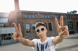 Teenage boy blowing bubble gum and showing peace sign