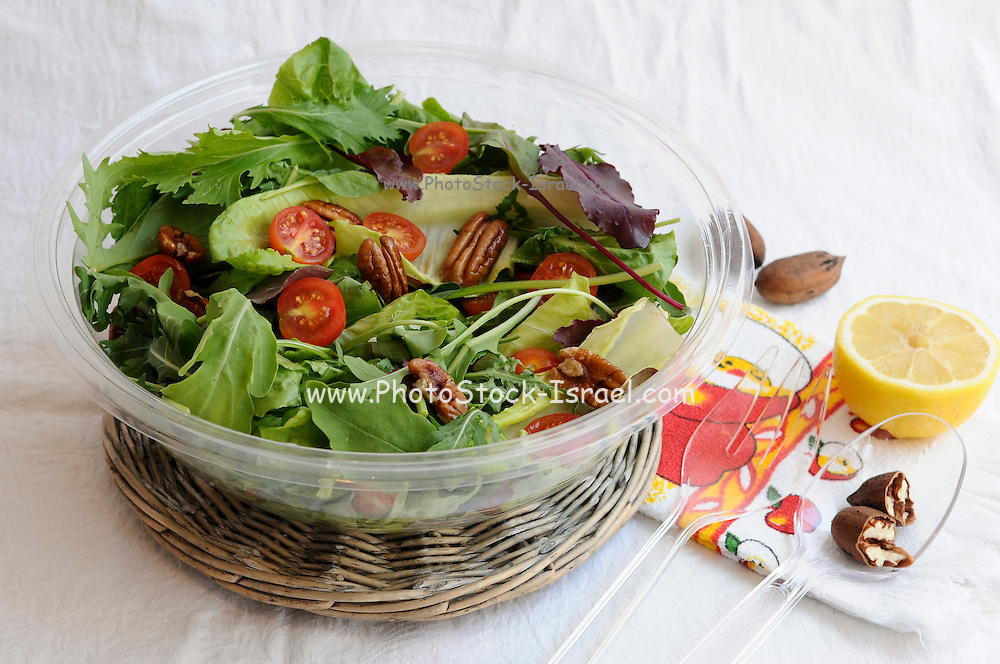 Green salad with lettuce, rocket (Arugula) and cherry tomatoes and pecan nuts