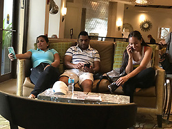 September 9, 2017 - Florida, U.S. - People use their cellphones in a lobby. A hurricane-force wind gust was recorded in the Florida Keys late Saturday night, the first sign of deadly Hurricane Irma's impending landfall on the U.S. mainland. The weather service said the Smith Shoal Light station recorded a 74 mph wind gust on Saturday night. (Credit Image: © Arnold Drapkin/ZUMA Wire/ZUMAPRESS.com)
