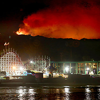 The Loma Fire raging on the Santa Cruz Mountains summit between Morgan Hill and Watsonville, California is seen beyond the Giant Dipper Roller Coaster at the Santa Cruz Beach Boardwalk on Monday September 26, 2016. Photo by Shmuel Thaler     <br />shmuel_thaler@yahoo.com  www.shmuelthaler.com