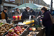Daily life continues but not as as normal with some rules and restrictions in Hackney on 21st March 2020 in London, United Kingdom. Broadway market on a Saturday morning. Fruit and vegetable stall with sellers wearing facemasks.