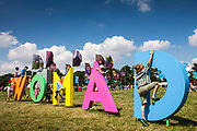 Kids climbing on the WOMAD sign. WOMAD 2014, festival of world music and dance, Charlton Park, Wiltshire. UK.