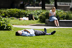 © Licensed to London News Pictures. 28/06/2019. London, UK.  Office workers and tourists relax at lunchtime during the warm and sunny weather near St Paul's Cathedral in London on Friday lunchtime. A heatwave is forecast across much of the UK tomorrow, with temperatures in the capital expected to reach 33 degrees celcius.  Photo credit: Vickie Flores/LNP