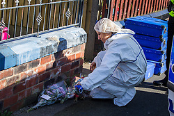 © Licensed to London News Pictures . 10/03/2014 . Farnworth , UK . A forensic examiner moves flowers in front of the house . Police and forensic scenes of crime examiners at a house on Kildare Street , Farnworth , where the body of 40 year old Marc Jepson was discovered on 5th March , as Greater Manchester Police announce that they have arrested two people as part of their murder enquiry . A 27 year old man and a 63 year old woman are in police custody for questioning . Photo credit : Joel Goodman/LNP