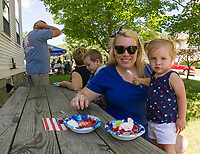 Brittney and Alexis Peterson enjoy a strawberry shortcake in the shade following the Gilmanton 4th of July parade on Tuesday morning.  (Karen Bobotas/for the Laconia Daily Sun)