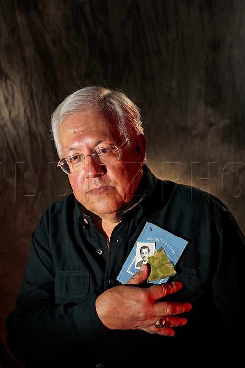 Wilfredo Figueras holds a Cuban passport, a sliver of his combat fatigues and a portrait of himself taken months before the Bay of Pigs invasion in Cuba. His hand was hit by shrapnel during the battle. He is a member of the Bay of Pigs Veterans Association, Brigade 2506.
