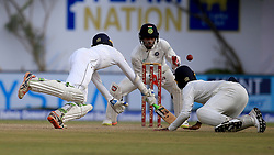 July 27, 2017 - Galle, Sri Lanka - Sri Lankan cricketer Upul Tharanga(L) dives in as Indian Wicket keeper Wriddhiman Saha (2L) awaits for the ball to complete a successful run out chance  the 2nd Day's play in the 1st Test match between Sri Lanka and India at the Galle International cricket stadium, Galle, Sri Lanka on Thursday 27 July 2017. (Credit Image: © Tharaka Basnayaka/NurPhoto via ZUMA Press)