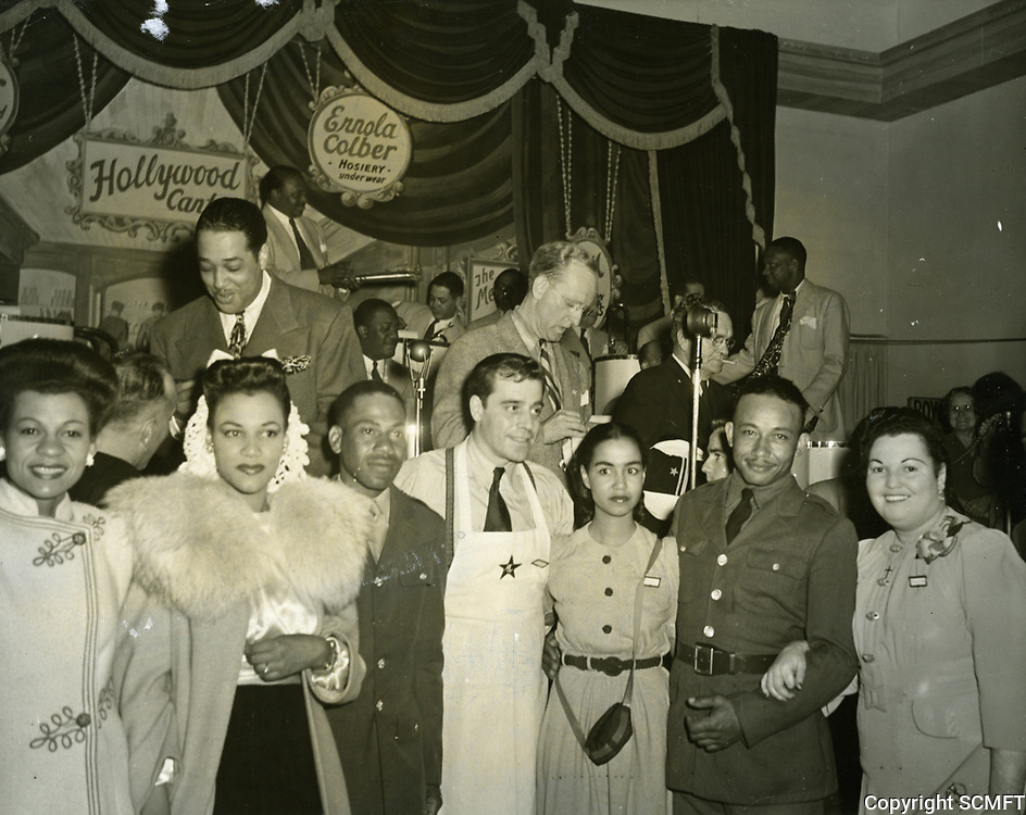 10/8/42 As Duke Ellington is on stage with Kay Kyser, Jack LaRue (with apron) poses with negro hostesses and servicemen. Racial segregation was never tolerated at the Canteen.