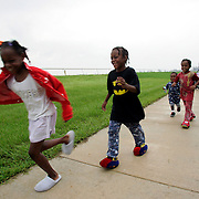 WEST PALM BEACH, FL - September 6, 2005:  My-Shelle Johnson, 8, Kevin Johnson the 3rd, 7 yrs, Kevin Johnson the 4th, 5 yrs, and Kevin Johnson the 5th, 2 yrs, run down a path at a evacuation shelter in West Palm Beach, FL on Sept, 6, 2005 as their parents, Kevin Johnson the 2nd and Michelle Johnson follow behind. The shelter is called Palm Meadows and is a training facility for thoroughbred horses. The Johnson family evacuated New Orleans after being stranded for days in their flooded home and having to watch dead bodies float by. (Photo by Todd Bigelow/Aurora)