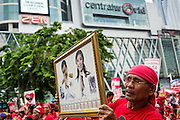 19 MAY 2013 - BANGKOK, THAILAND:   A Thai Red Shirt holds up photos of ousted Prime Minister Thaksin Shinawatra and his sister, current Primie Minister Yingluck Shinawatra during a Red Shirt rally in Ratchaprasong Intersection honoring Red Shirts killed by the Thai army in 2010. The man is standing in front of Central World, the Bangkok mall that was burned down during the crackdown. It reopened in 2011. More than 85 people, most of them civilians, were killed during the Thai army crackdown against the Red Shirt protesters in April and May 2010. The Red Shirts were protesting against the government of Abhisit Vejjajiva, a member of the opposition who became Prime Minister after Thai courts ruled the Red Shirt supported government was unconstitutional. The protests rocked Bangkok from March 2010 until May 19, 2010 when Thai troops swept through the protest areas arresting hundreds.  PHOTO BY JACK KURTZ