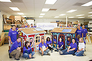 FedEx employees pose for a photo after volunteering for eight hours building two playhouses from scratch at Habitat For Humanity in Milpitas, Calif., on Sept. 11, 2012.  One playhouse (right) was presented and donated to the Veterans Supportive Services Agency, Inc.  Photo by Stan Olszewski/SOSKIphoto.