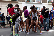 Dancers during the main parade at the Notting Hill Carnival in West London. The Notting Hill Carnival is an annual event which since 1964 has taken place each August, over two days (the August bank holiday Monday and the day beforehand). It is led by members of the West Indian / Caribbrean community, particularly the Trinidadian and Tobagonian British population, many of whom have lived in the area since the 1950s. The carnival has attracted up to 2 million people in the past, making it the second largest street festival in the world. The celebration centres around a parade of floats, dancers and sound systems.