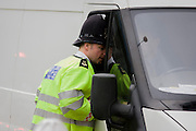 A officer from the City of London police, questions a white van driver at a checkpoint looking for suspect vehicles and drivers entering at Aldgate, one the city entrance points into the Square Mile, the capital's financial and historic heart, founded by the Romans in 43AD.