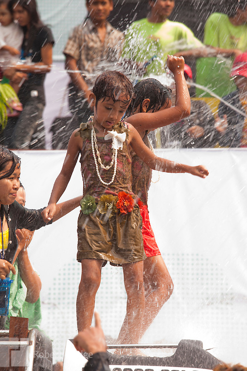 Mandalay, Myanmar- April 14, 2013: Two children are among the celebrants who climb atop vehicles to dance and get hosed with water during Myanmar's Thingyan Water Festival. Thingyan is held in April, one of the hottest months of the year in Myanmar. The water festival marks the country's New Year celebration and the festival includes lots of drinking, singing, dancing and theater. Wherever you are you are likely to get doused with water as the Burmese see this as a cleansing of the previous year's sins and bad luck and a blessing for good luck and prosperity in the year ahead. In the major cities of Mandalay and Yangon, large platforms are erected along major roadways and are equipped with high powered water hoses. The platforms, sponsored by large corporate donors, also have dance stages and play the latest pop and hip hop music. Thousands of residents pour into the streets by foot, motorbike and flatbed truck to get hosed under the platforms while they drink and dance. Many of the young celebrants wear their best clubbing clothes. And many of the party goers are men, having left their wives and girlfriends at home.