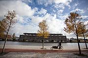 In Haarlem rijdt een bakfietser op het fietspad langs de Spaarne.<br /> <br /> In Haarlem a cyclist in a bike lane passes the Spaarne.