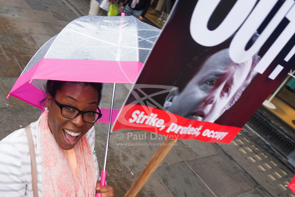 """London, July 10th 2014. A woman demnds """"Cameron out!"""" as thousands of striking teachers, government workers and firefighters march  through London in protest against cuts and working conditions."""
