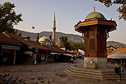 A square in Sarajevo's Old Town showing the Sebilj and the minaret of the Gazi Husrev-beg Mosque