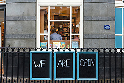 Edinburgh, Scotland, UK. 29 June, 2020. Many shops which have door access to the street are allowed to open for business in Scotland today. Despite cool temperatures, high winds and often heavy rain, some shops had queues outside in the morning. Tourist shops on the Royal Mile remained closed however, due to a lack of tourists,  and streets in the Old Town remained empty.  Pictured; Topping and Company bookshop is now open.  Iain Masterton/Alamy Live News