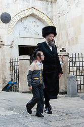 © Licensed to London News Pictures. 02/05/2014. Jerusalem, Israel. Jewish families hurry through the Armenian Quarter of the Old City of Jerusalem past the Armenian Catholic Chapel at approx 6.30pm in order to reach The Western Wall  in time for the start of the Shabbat (the Jewish sabbath).  Jewish custom sees the lighting of candles scheduled for 6.39pm this evening, shortly before the sunset when Shabbat commences.  The Western Wall is the most important shrine of the Jewish faith and is located in the Old City at the foot of the western side of Temple Mount.  The Old City is comprised of four Quarters - the Jewish, Muslim, Christian and Armenian. Photo credit : Richard Isaac/LNP
