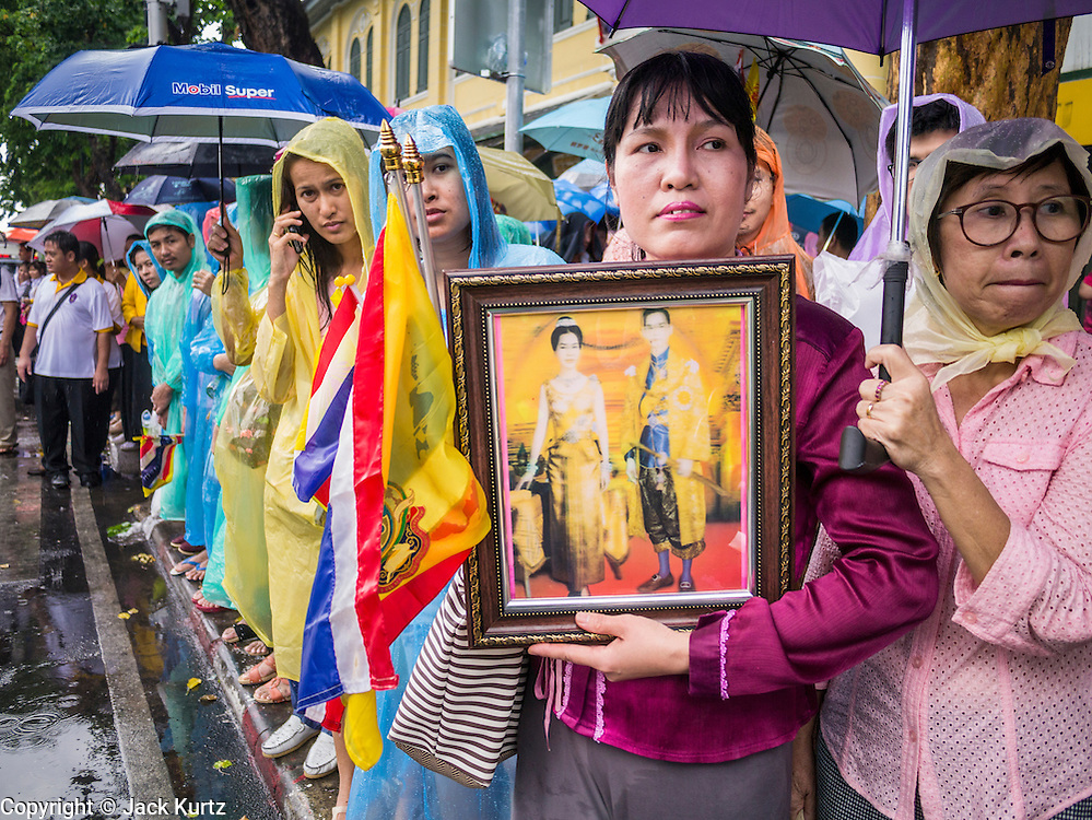 05 MAY 2013 - BANGKOK, THAILAND: A Thai woman holds an old picture of Bhumibol Adulyadej, the King of Thailand, and his wife Queen Sirikit Sunday while she waits for them at the Grand Palace Sunday. The King and Queen, who are both hospitalized and in poor health, did not attend Sunday's event. May 5 marks the 63rd anniversary of the Coronation of His Majesty King Bhumibol Adulyadej. The day is celebrated as a national holiday; since this year it falls on a Sunday, it will be observed on Monday May 6, and as such all government offices and commercial banks will close for the day. HM King Bhumibol Adulyadej is the longest reigning monarch in the world. Each year on the 5th of May, the Kingdom of Thailand commemorates the day when, in 1950, the Coronation Ceremony was held for His Majesty King Bhumibol Adulyadej, the 9th in the Chakri Dynasty (Rama IX). On the 5th of May, His Majesty conducts a merit making ceremony, presenting offerings to Buddhist monks, and leads a ?Wien Thien? ceremony, walking three times around sacred grounds at the Temple of the Emerald Buddha. PHOTO BY JACK KURTZ