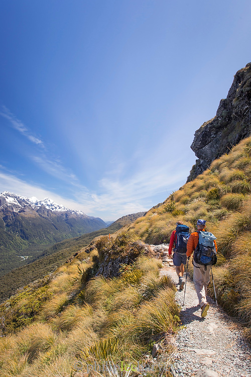 View of two people hiking along the mountainside on the Routeburn Track, South Island, New Zealand