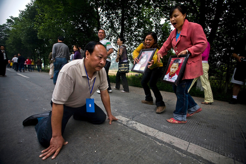 Jiang Guohua, the Communist Party secretary of Mianzhu city, kneels on the ground pleading with protesting parents, whose children were killed in a school collapse during China's recent devastating earthquake, not to complain to higher authorities, in Mianzhu, Sichuan province. Despite Jiang's pleas, the parents of the 127 children who died in the collapse kept marching Sunday and eventually met with higher officials, who told them the government would investigate.