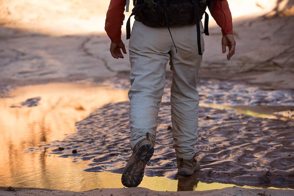 Backpacker walking by canyon pool, Cedar Mesa, Utah.