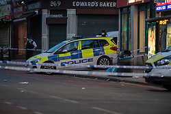 © Licensed to London News Pictures. 29/04/2021. London, UK. A police vehicle and police tape mark out the crime scene on High Road in Willesden following the fatal stabbing of a 40-year-old man. Police were called by London Ambulance Service at 17:11 BST to a report of a man suffering from stab wounds, despite the efforts of the emergency services the man was pronounced dead at the scene. Photo credit: Peter Manning/LNP