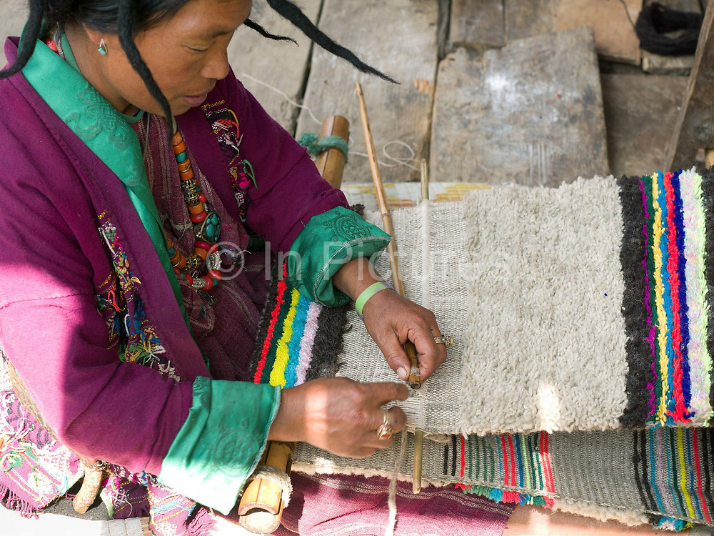 A Brokpa woman weaves a traditional sheep wool blanket on a backstrap loom in the remote and roadless village of Sakteng, Eastern Bhutan. The Brokpa, the semi-nomads of the villages of Merak and Sakteng are said to have migrated to Bhutan a few centuries ago from the Tshona region of Southern Tibet. Thriving on rearing yaks and sheep, the Brokpas have maintained many of their unique traditions and customs.