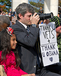 A spectator holds a sign as he takes photos during United States President Barack Obama's remarks in the Memorial Amphitheater at Arlington National Cemetery in Arlington, Virginia after laying a wreath at the Tomb of the Unknown Soldier on Veteran's Day, Friday, November 11, 2016.<br /> Credit: Ron Sachs / Pool via CNP