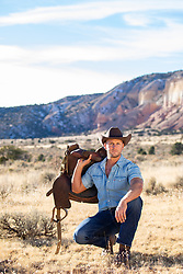 cowboy squatting down and holding a saddle on a rustic mountain ranch