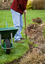 Redefining a lawn edge using a half moon shaped cutter. Also known as half-moon iron
