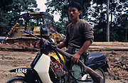 1989: Kelabit native, Fredrick Ngareng, in his early twenties, with shotgun and a Honda 50cc motorbike. Behind him is logging with caterpillar and logging camp. Near Long Napir, Limbang district, Sarawak, Borneo<br /> <br /> Tropical rainforest and one of the world's richest, oldest eco-systems, flora and fauna, under threat from development, logging and deforestation. Home to indigenous Dayak native tribal peoples, farming by slash and burn cultivation, fishing and hunting wild boar. Home to the Penan, traditional nomadic hunter-gatherers, of whom only one thousand survive, eating roots, and hunting wild animals with blowpipes. Animists, Christians, they still practice traditional medicine from herbs and plants. Native people have mounted protests and blockades against logging concessions, many have been arrested and imprisoned.