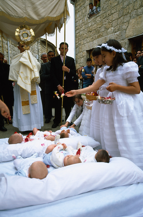 After the devil incarnate, El Colacho, on the last day of the Fiesta del Colacho, has jumped over the babies born during the year, the priest holds up the monstrance containing the host while young girls scatter petals over the infants, in Castrillo de Murcia, Burgos province, Spain. The Fiesta del Colacho is held every year at the time of the Catholic feast Corpus Christi.