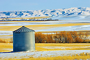 Grain bin and Big Muddy Badlands in background in winter<br /> south of Bengough<br /> Saskatchewan<br /> Canada