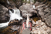 Ethan Welty relaxes with his hiking boots on a log by a waterfall up the Big Thompson River canyon in Rocky Mountain National Park, Colorado.