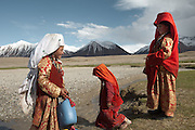 Tella Bu, youngest daughter of the late Khan, and her sisters are fetching water at the Aksu river, nearby their autumn camp. Daily life at the Khan (chief) autumn camp (called Teramo Jai - place of Autumn), beside the Aksu river...Trekking through the high altitude plateau of the Little Pamir mountains (average 4200 meters) , where the Afghan Kyrgyz community live all year, on the borders of China, Tajikistan and Pakistan.