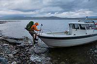 Hiker climbs about small boat ferry across lake Riebnes on Kungsleden Trail, Lapland, Sweden