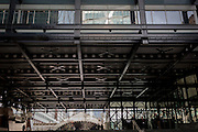 City workers walk beneath the girders of Thatcherite architecture, on 16th February 2017, at Broadgate in the City of London, England.