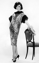 """Natalie Wood, wearing a theatre coat fashioned of gold, black and crimson brocade, featuring short sleeves and collar of ranch mink. She is set to star in Metro-Goldwyn-Mayer's """"All the Fine Young Cannibals""""."""