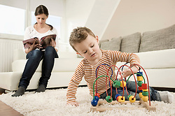 Boy playing game while mother sitting on sofa