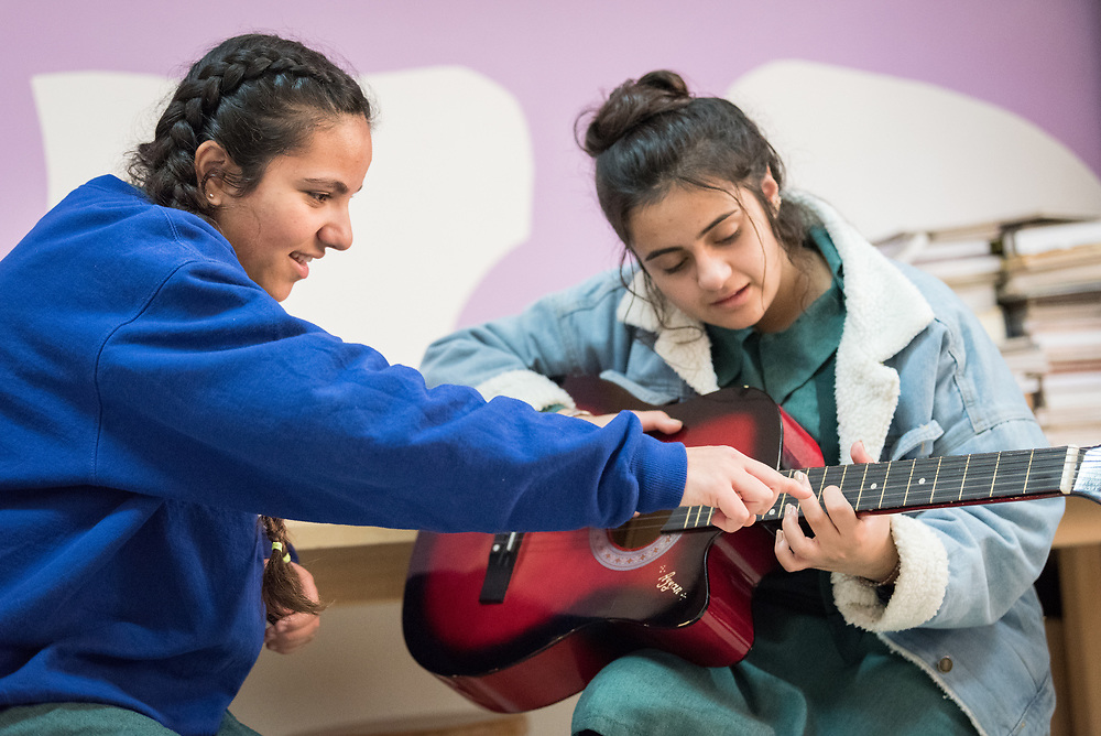 18 February 2020, Amman, Jordan: Sixteen-year-old Ayyan plays the guitar in the Talent Room of Rufaida Al Aslamieh Primary Mixed School in the Sahab district, receiving instruction from 15-year-old student Rena Amlaharmeh. The school serves more than 1,000 students from kindergarten up to 10th grade, most of them girls from Jordan but also some from Syria and other countries, and, in the lower grades, also boys. With support from the Lutheran World Federation, the school has refurbished its rooms and buildings and introduced a 'Talent Room' in order to nurture the children's creativity. This type of learning environment is otherwise rare in Jordanian public shools.