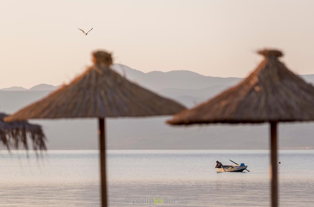Fisherman checking fishing net in harbor at sunrise, Skala Kallonis, Lesbos, Greece