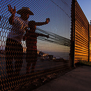 View from another world, a father and son peer through the international boundary into the United States from Tijuana, Mexico. <br /> <br /> Photo registered with the US Copyright Office. © Todd Bigelow<br /> <br /> Please contact Todd Bigelow directly with your licensing requests. PLEASE CONTACT TODD BIGELOW DIRECTLY WITH YOUR LICENSING REQUEST. THANK YOU!