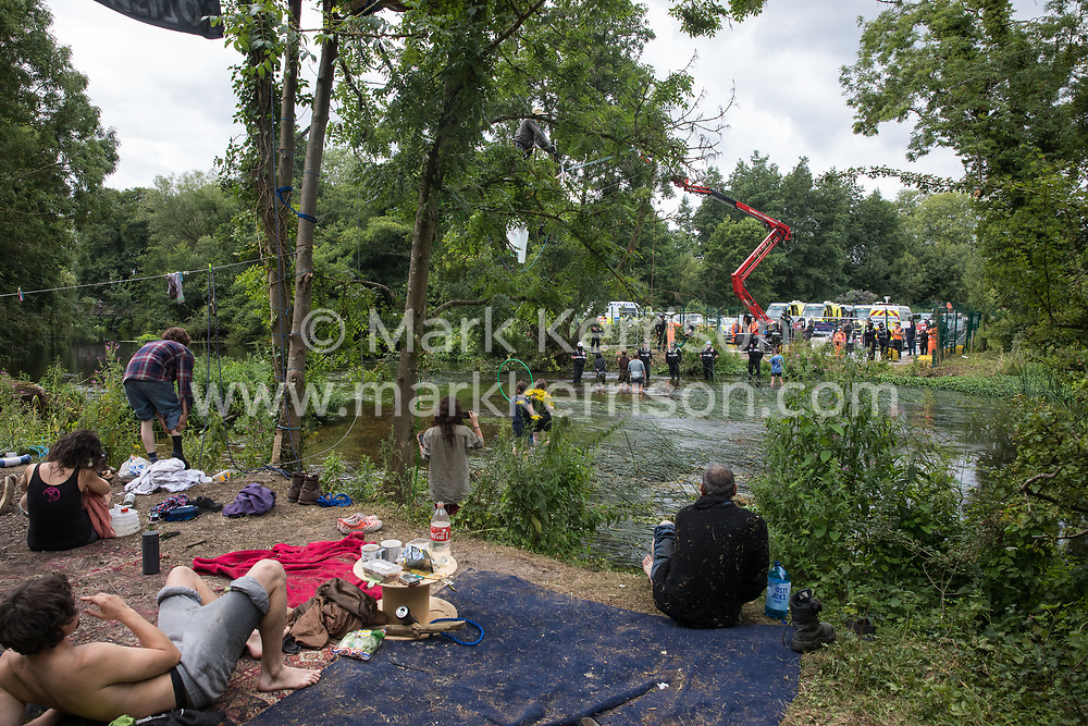 Denham, UK. 24 July, 2020. Environmental activists from HS2 Rebellion, including some on a line, try to protect an ancient alder tree from destruction in connection with works for the HS2 high-speed rail link in Denham Country Park. A large policing operation involving the Metropolitan Police, Thames Valley Police, City of London Police and Hampshire Police as well as the National Eviction Team was put in place to enable HS2 to remove the tree.