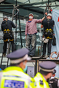 """Police form a line to observe the process of removing a protestors from Police Protest Removal Unit, after a father and ex-teacher climbed onto the canopy above the front door of the Department for Business and Energy building where he spray-painted '4 degrees = Mass murder' and unfurled a banner reading 'Act Now For All Our Children' on Monday, Sept 7, 2020. He said: """"My youngest child is only one. Within her lifetime scientists tell us that we are likely to see 4 degrees of global warming he continued. <br /> Environmental nonviolent activists group Extinction Rebellion enters its 7th day of continuous ten days protests to disrupt political institutions throughout peaceful actions swarming central London into a standoff, demanding that central government obeys and delivers Climate Emergency bill. (VXP Photo/ Vudi Xhymshiti)"""